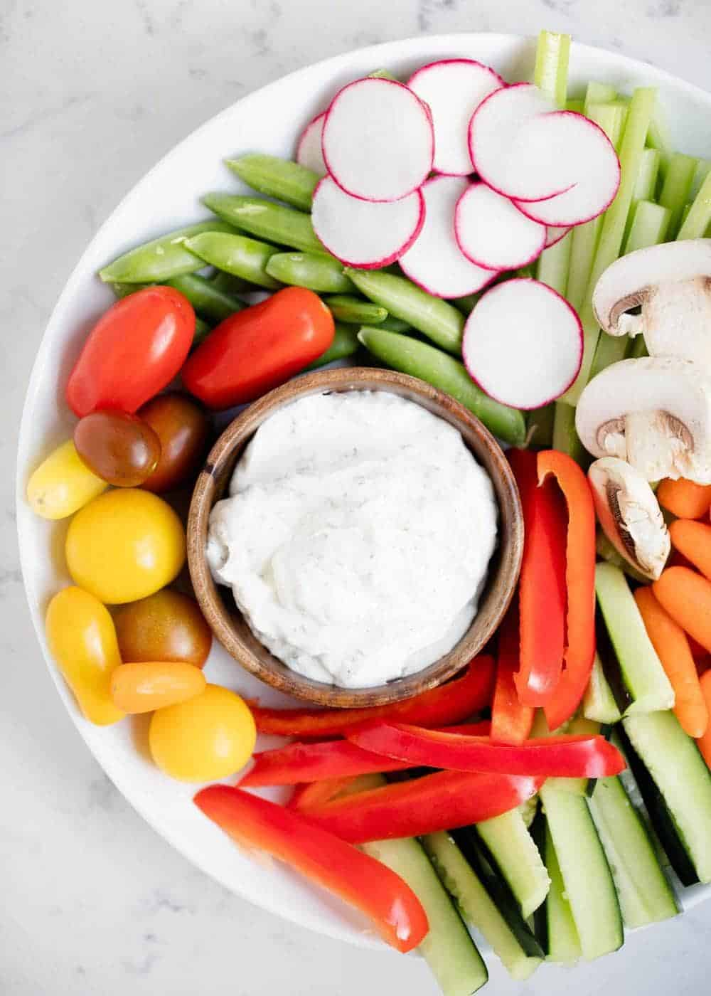 dill vegetable dip and fresh veggies on a white plate