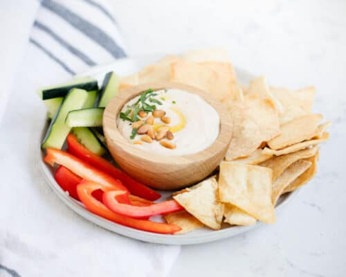 bowl of white bean hummus on a plate with fresh sliced veggies and pita chips