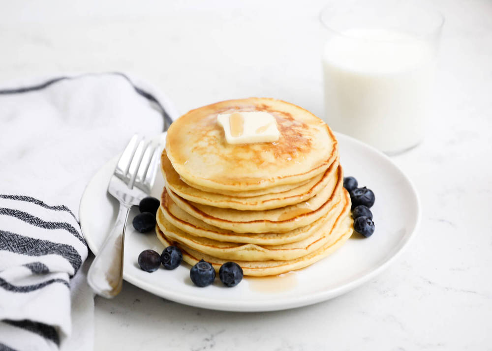 plate of ricotta pancakes with butter, syrup and blueberries