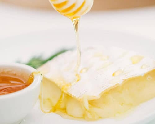 drizzling honey onto baked brie with a honey dipper