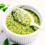pesto sauce in a white bowl with a spoon