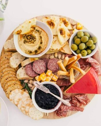 round charcuterie board with crackers, meats, cheeses and dips