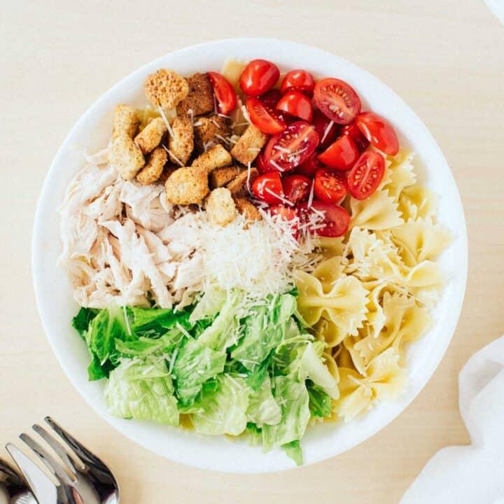 ingredients for caesar pasta salad in large white bowl