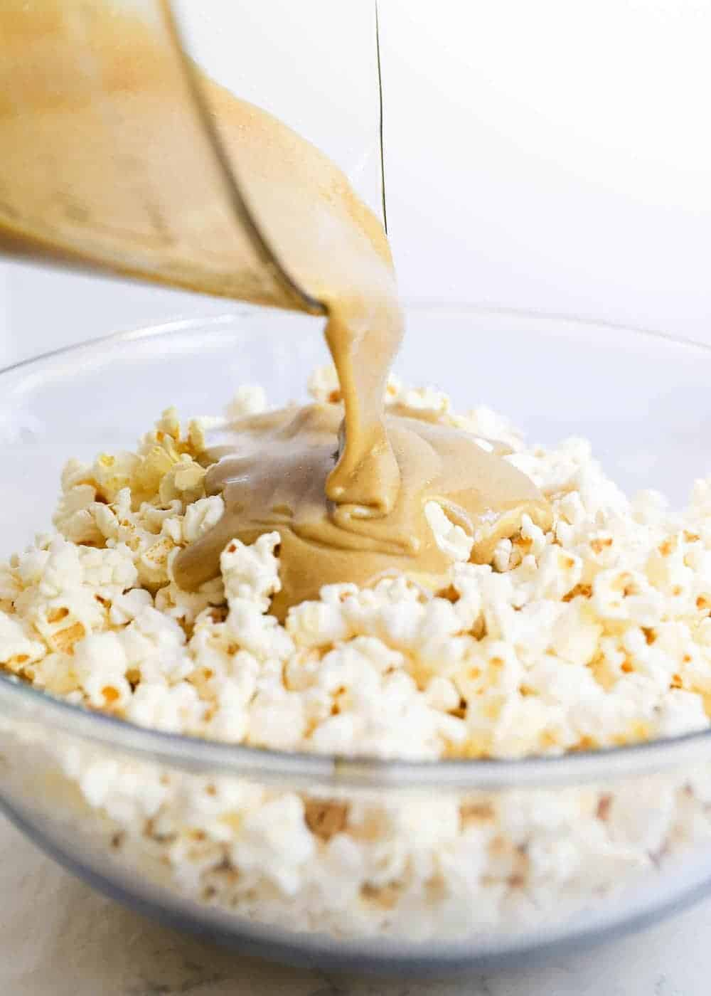 pouring caramel into bowl of popcorn