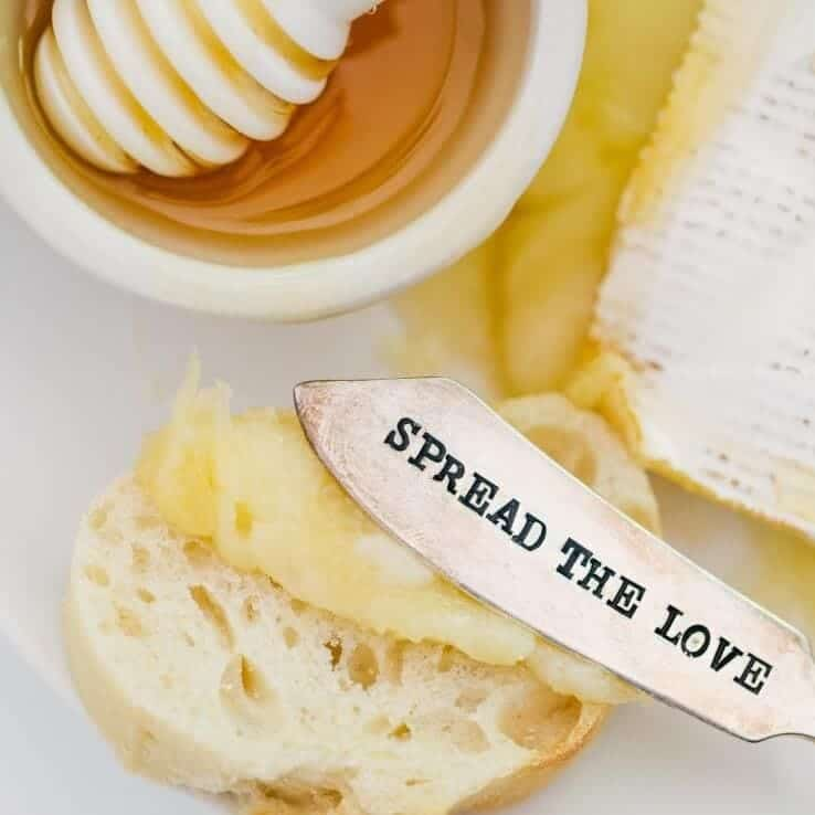 "spreading baked brie on crostini with ""spread the love"" knife"