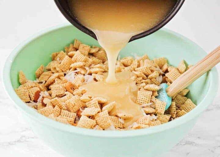 pouring the sugar mixture over chex mix
