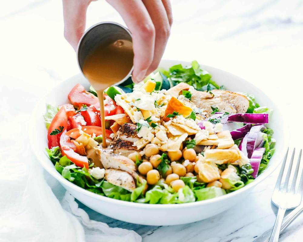 pouring balsamic over mediterranean salad