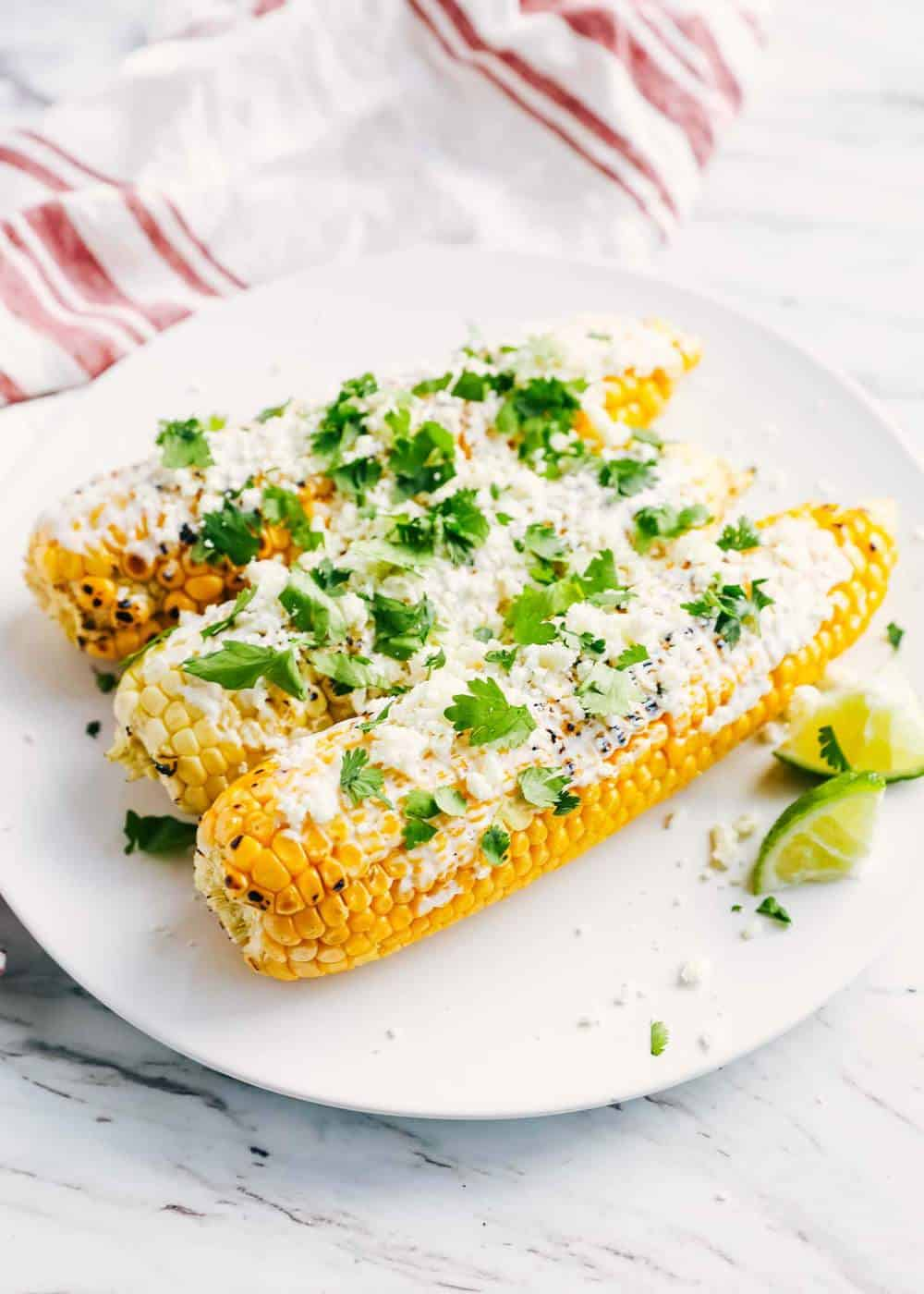 Mexican corn with cilantro on white plate