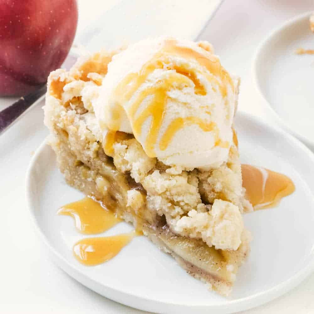 slice of apple pie on a white plate with ice cream and caramel