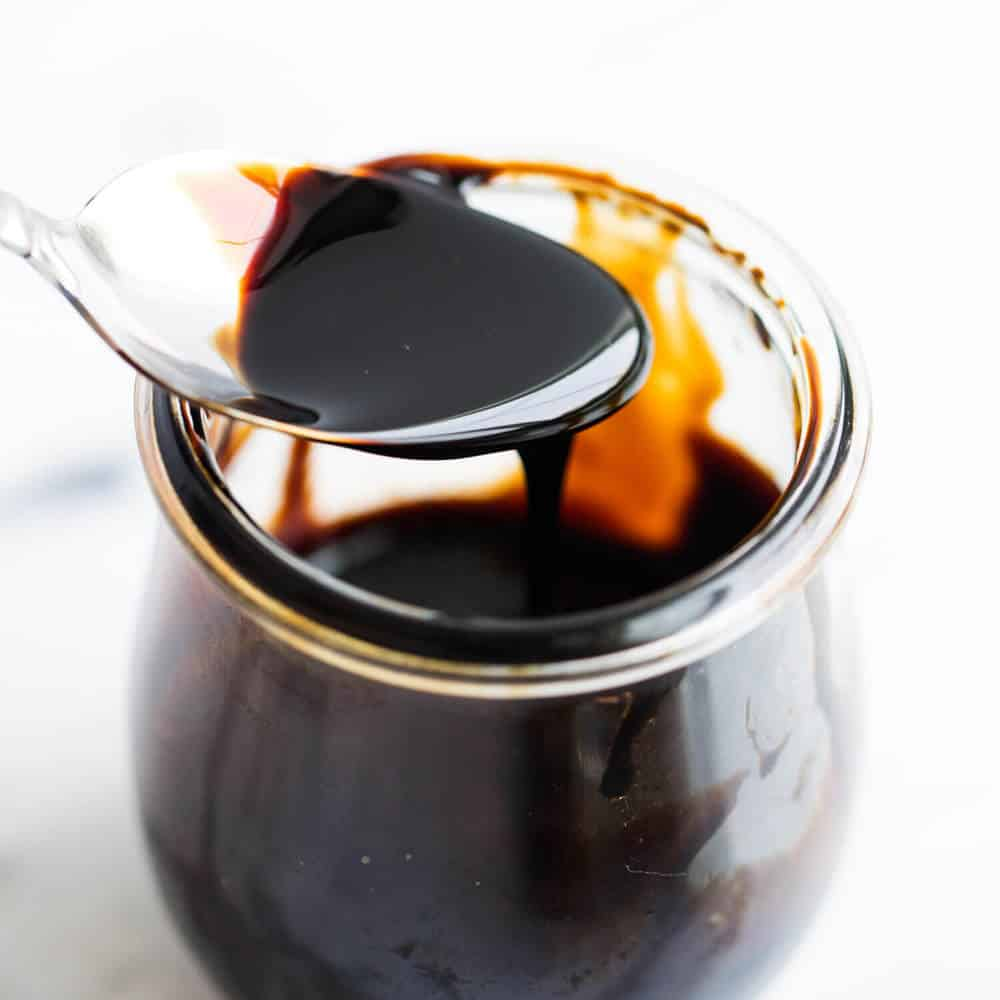 spoonful of balsamic glaze dripping into a glass jar