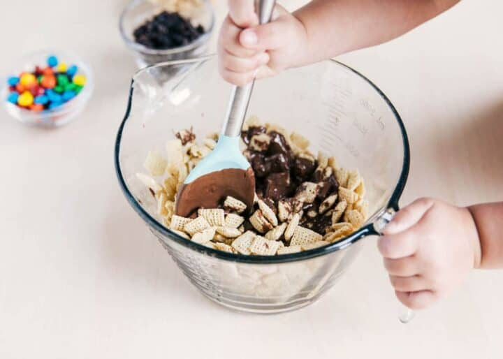 toddler mixing Chex cereal and melted chocolate in a mixing bowl with a spoon
