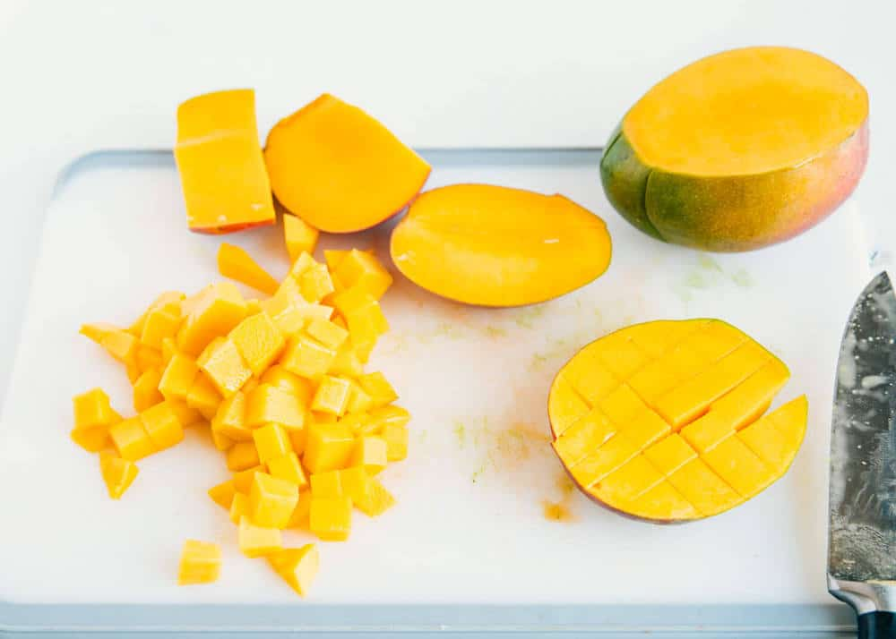 cutting mangoes on a cutting board for mango salsa