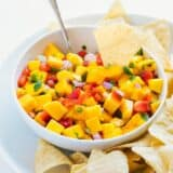 dipping a chip into a bowl of mango salsa