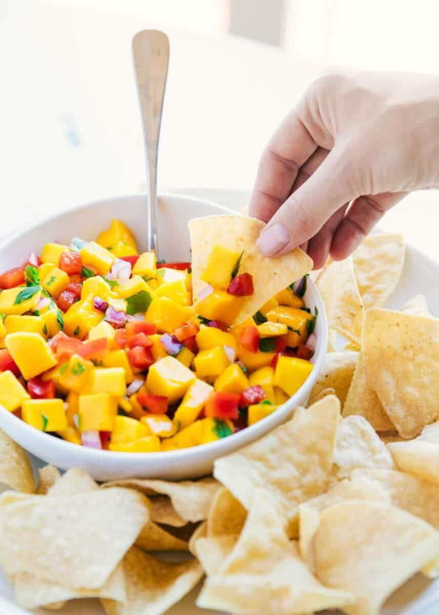 dipping a tortilla chip in a bowl of mango salsa