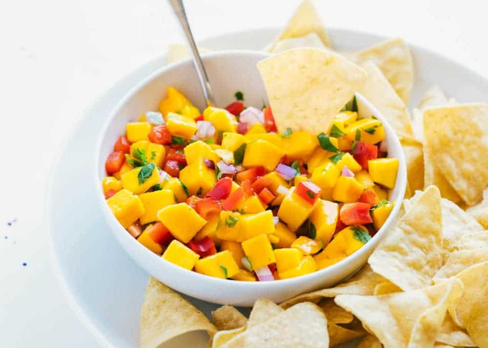 dipping a chip in a bowl of mango salsa