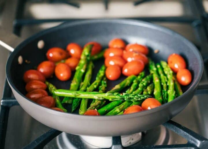 sauteing tomatoes and asparagus on skillet