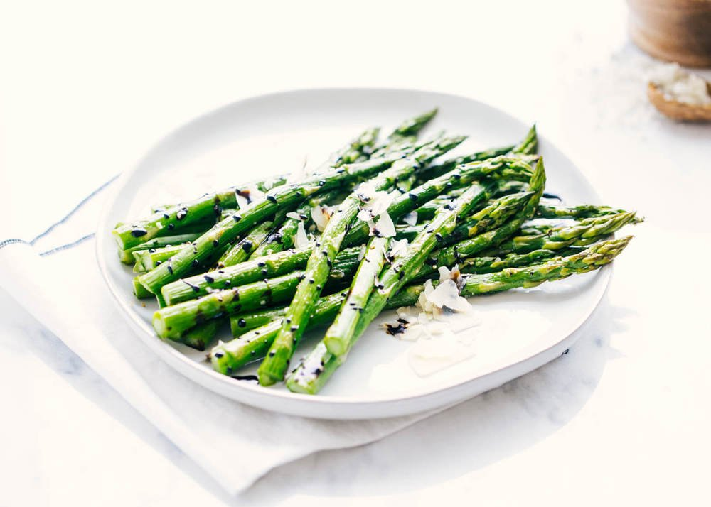 roasted asparagus on a plate with balsamic glaze and fresh parmesan