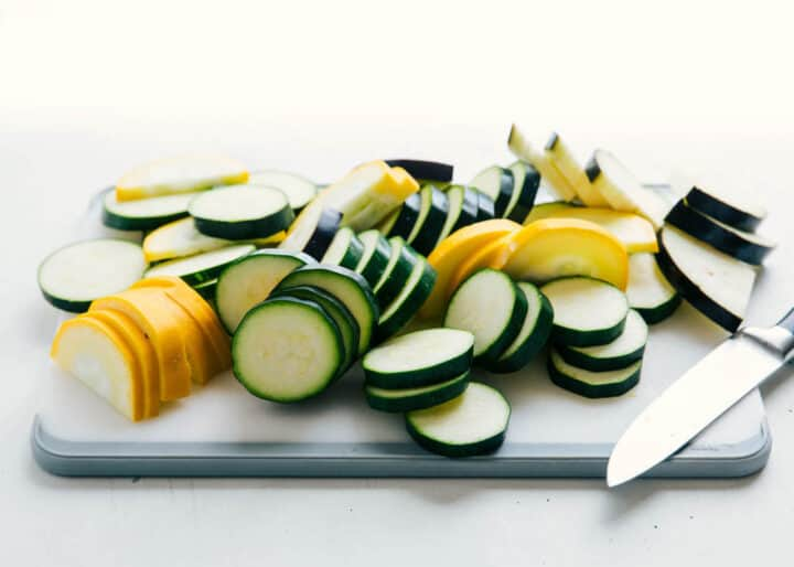 sliced zucchini squash on a white cutting board
