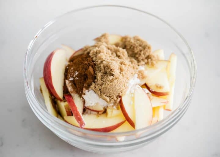 bowl of sliced apples with spices and sugar on top