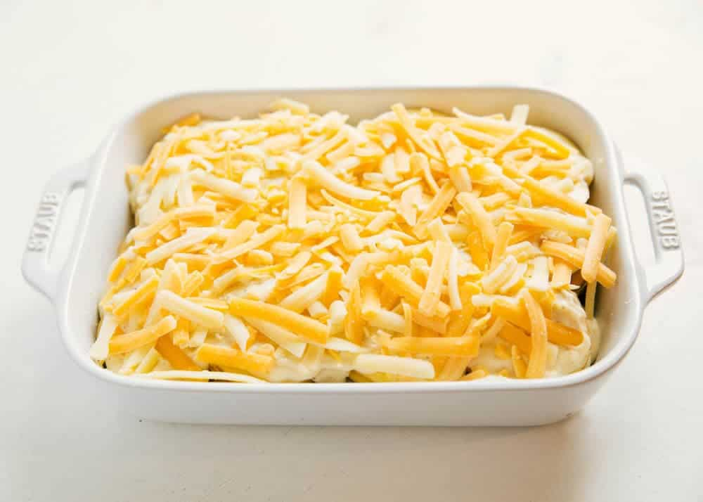 uncooked scalloped potatoes in a baking dish with cheese on top