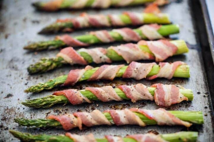 asparagus wrapped in bacon on baking sheet