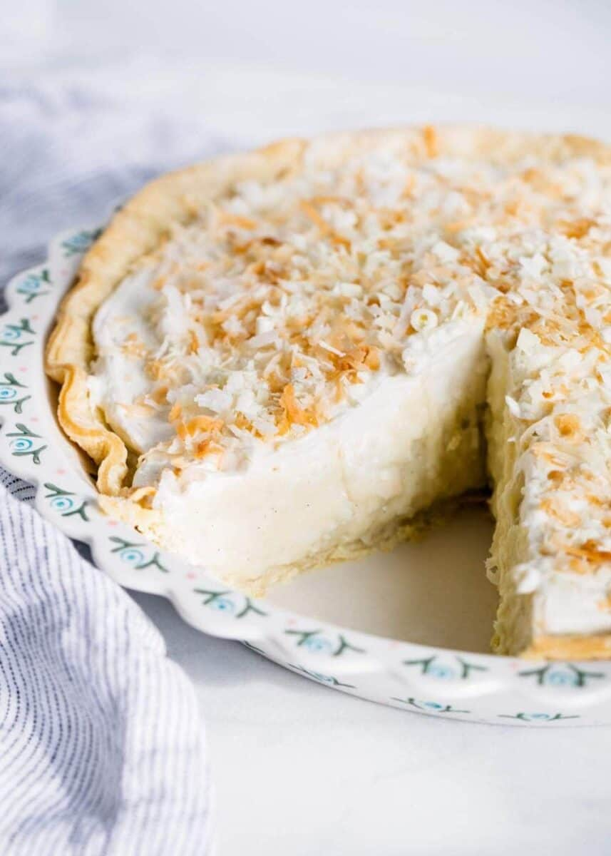 coconut cream pie in pan with slice taken out
