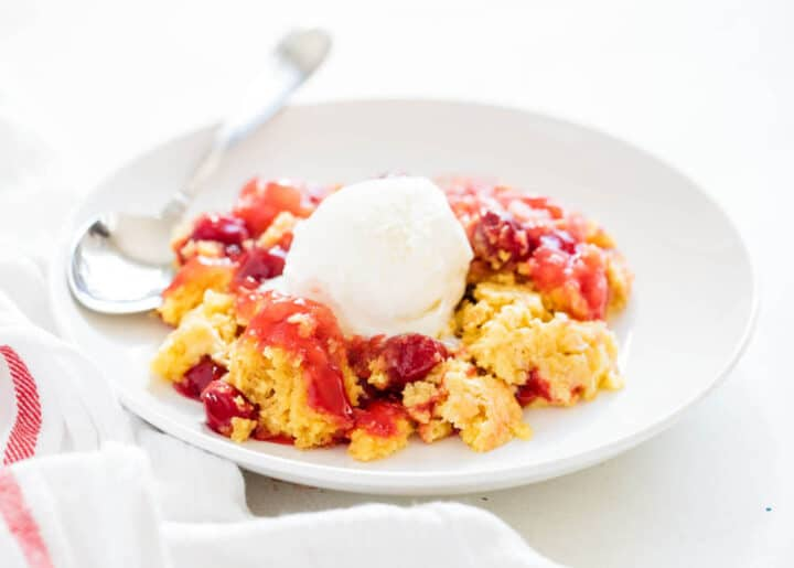 cherry dump cake on a plate with a scoop of vanilla ice cream