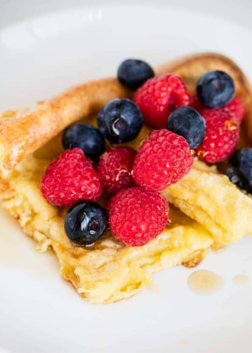 german pancakes topped with syrup and berries