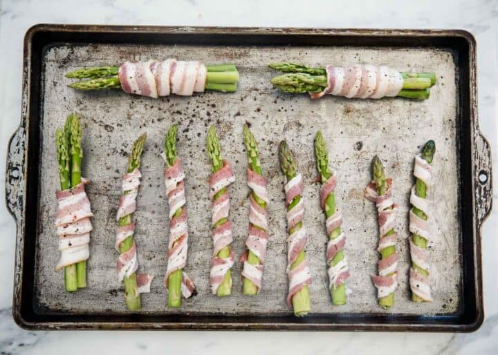 bacon wrapped asparagus on baking sheet