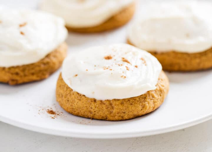 pumpkin cookies with cream cheese frosting on top