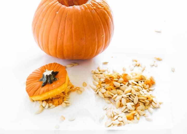 scooping pumpkin seeds out of pumpkin