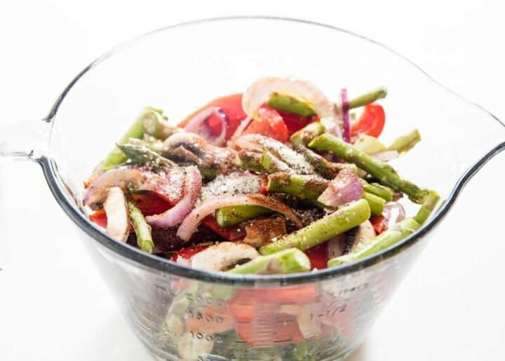 raw vegetables in a glass measuring bowl with spices on top