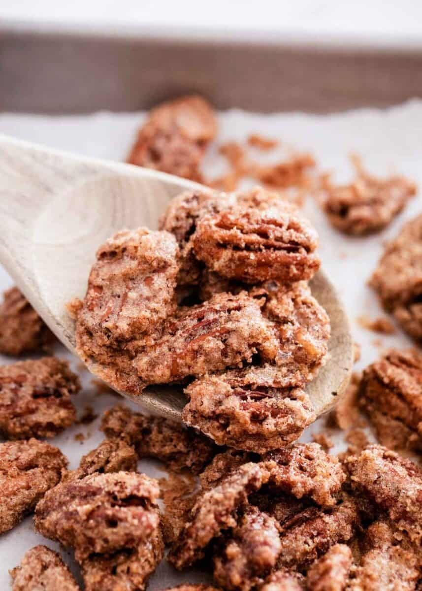 candied pecans on baking sheet with wooden spoon