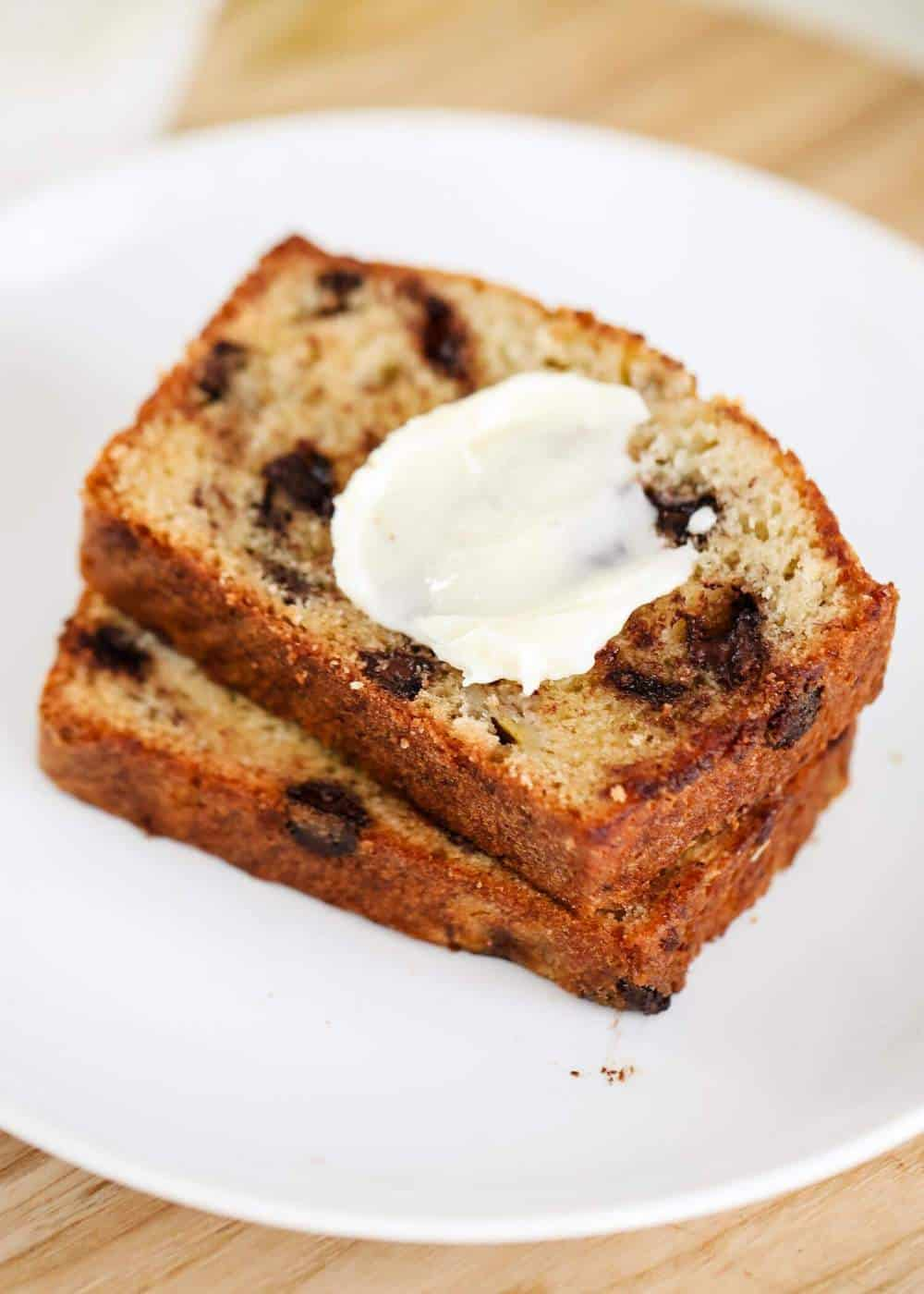 chocolate chip banana bread on a white plate with butter on top