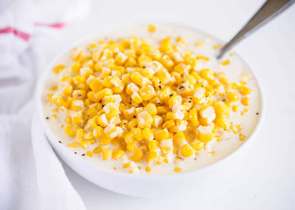 creamed corn in a white bowl with a spoon