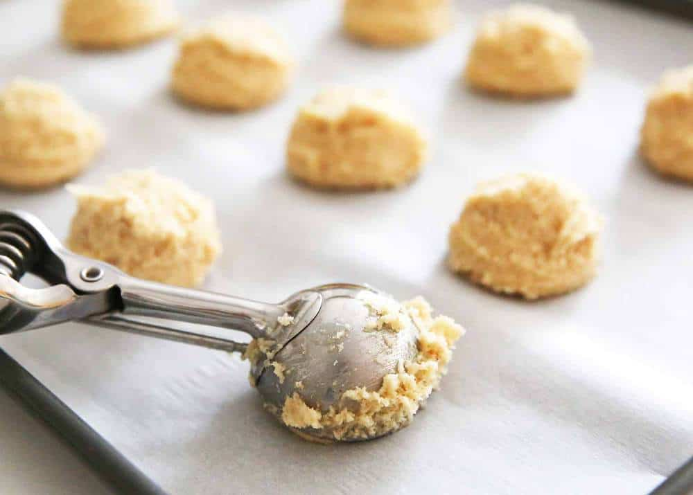 scooping eggnog cookie dough onto baking sheet with cookie scoop