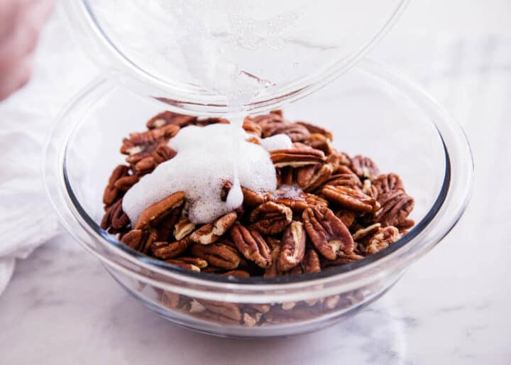 Pouring egg whites over bowl of pecans