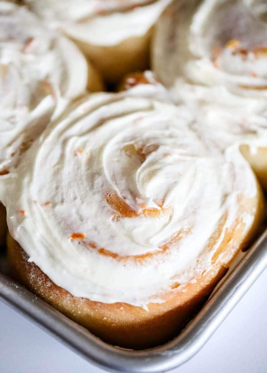 close up of a frosted orange roll