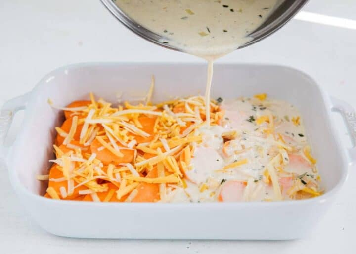 pouring rosemary sauce over scalloped sweet potatoes