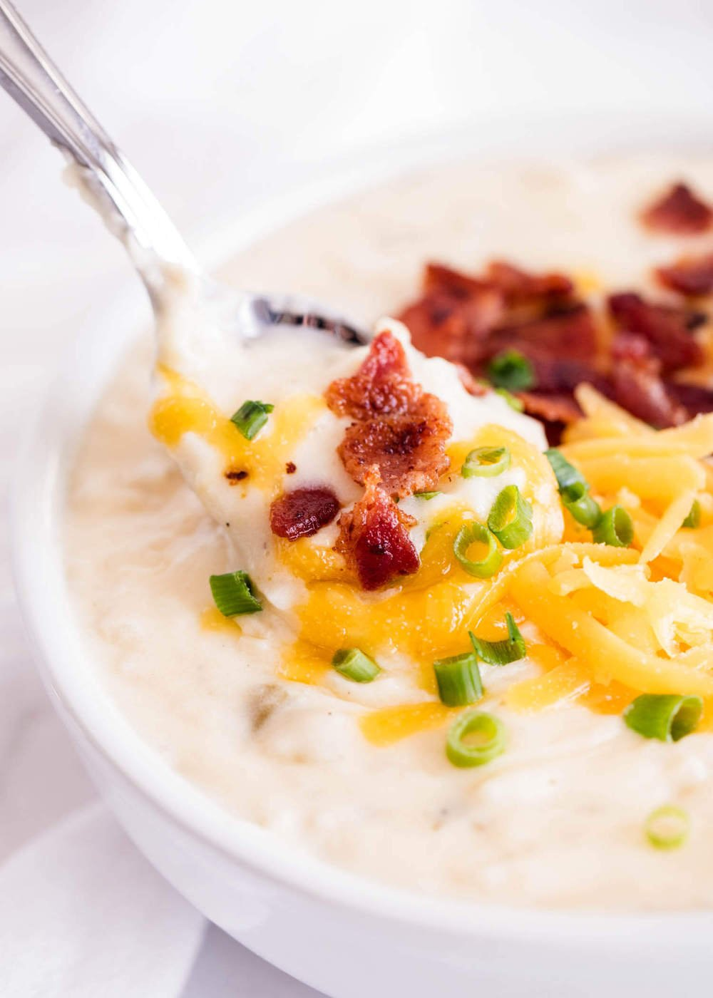 bowl of slow cooker potato soup with cheese, bacon and chives
