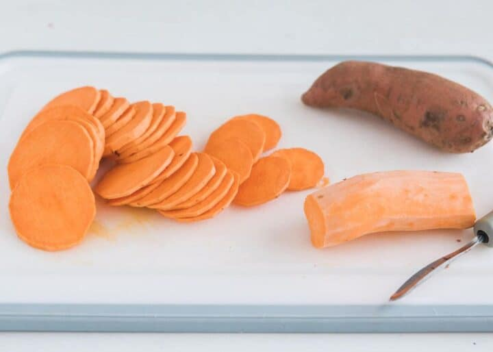 slicing sweet potatoes into rounds on cutting board