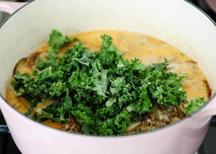 adding fresh kale in zuppa toscana soup