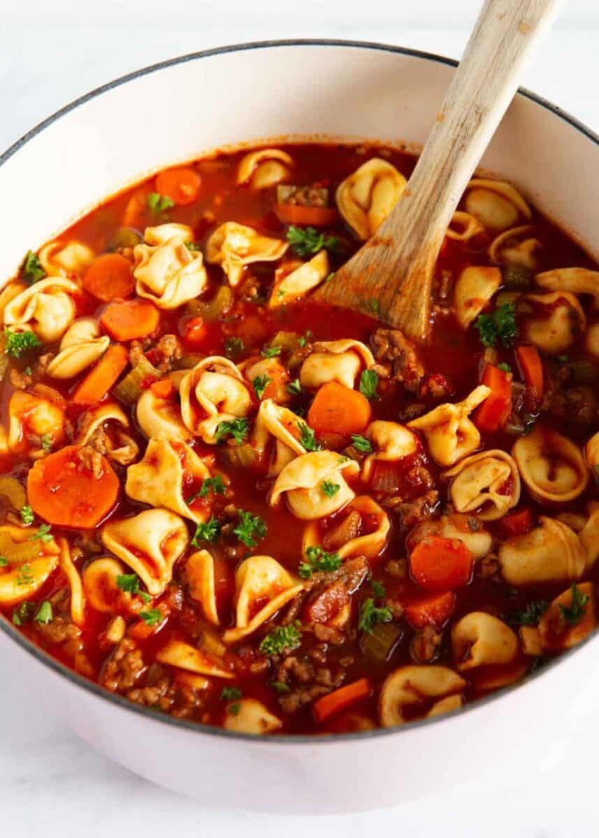 sausage and tortellini soup in pot with wooden spoon