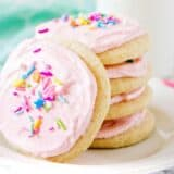 stacked sugar cookies with pink frosting and sprinkles