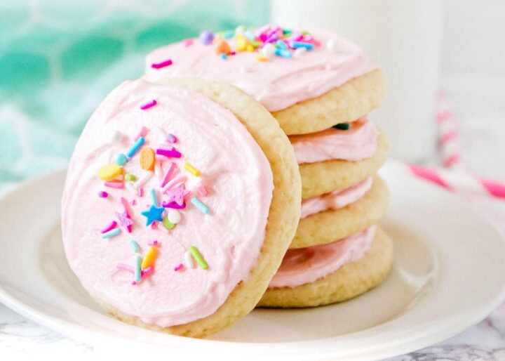 a stack of frosted sugar cookies on plate
