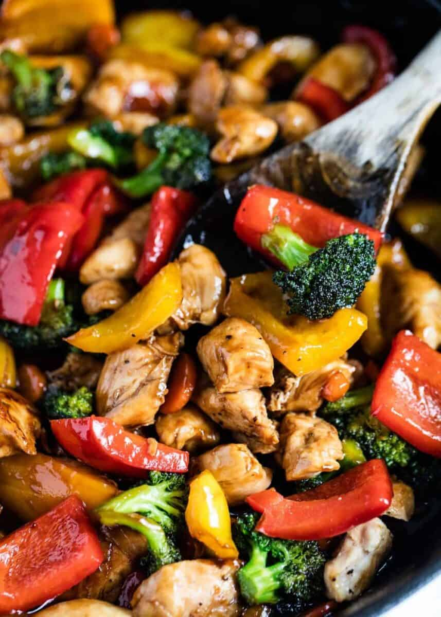 close up of chicken and vegetable stir fry with wooden spoon