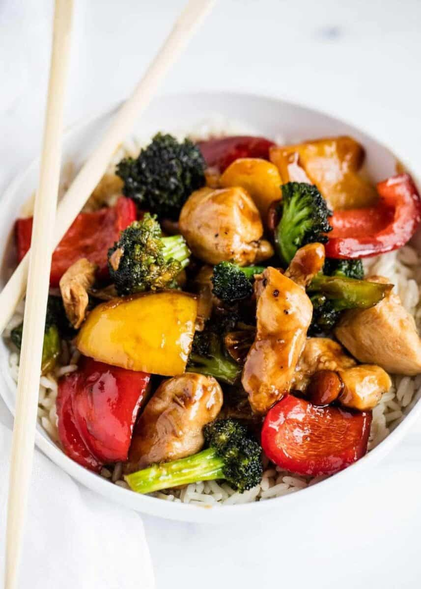 chicken and vegetable stir fry in bowl with chopsticks