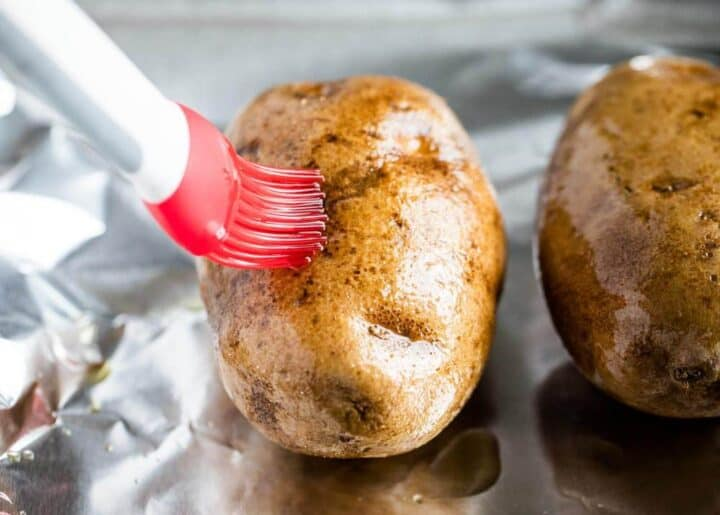 brushing olive oil on a baked potato