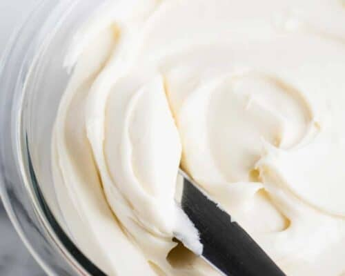 spreading cream cheese frosting with knife