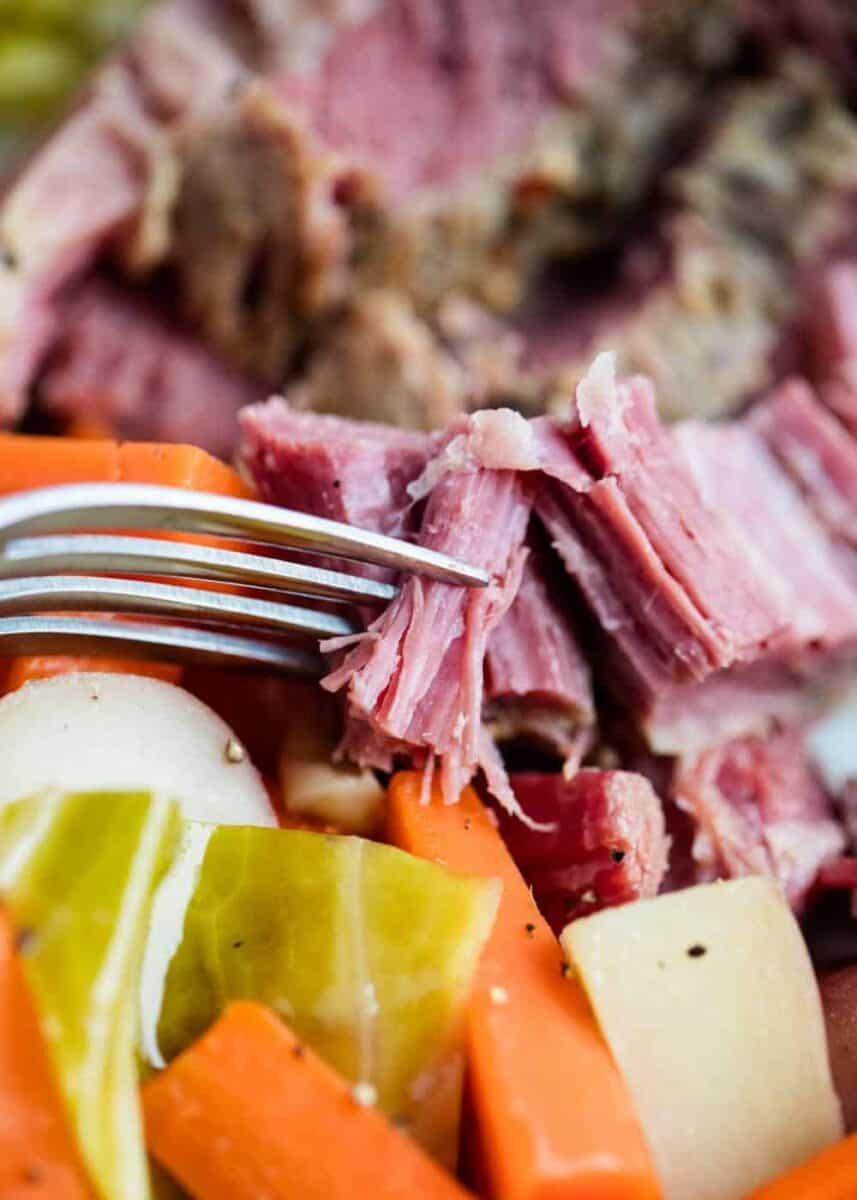 close up of corned beef and cabbage on fork